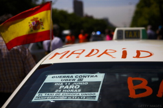 A Spanish flag flies from a taxi cab during a demonstration by cabbies to protest against the Uber Technologies Inc. taxi app in central Madrid, Spain, on Wednesday, June 11, 2014. Uber, the car-sharing service that's rankling cabbies across the U.S., is fighting its biggest protest yet from European drivers who say the smartphone application threatens their livelihoods. Photographer: Angel Navarrete/Bloomberg via Getty Images